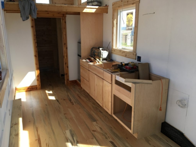 THE KITCHEN CABINETS ARE BEING INSTALLED